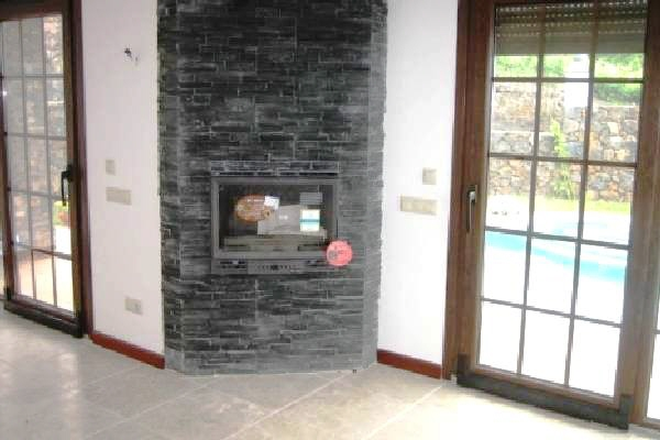 Wohnbereich mit Kamin und Zugang zur Terrasse