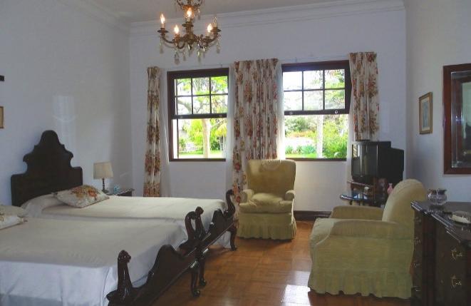 Schlafzimmer mit zwei Betten und Sesseln