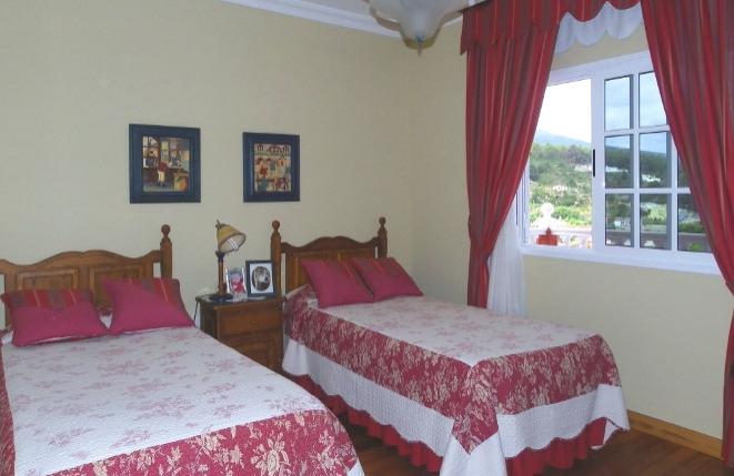 Gemütliches Schlafzimmer mit zwei Betten, Stuckdecke und Panoramameerblick