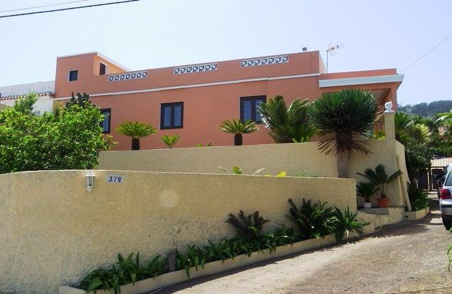 Frontansicht mit den Terrassen neben und vor dem Haus