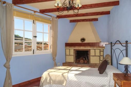 Wunderschönes Schlafzimmer mit hellem Wohnbereich und Kamin
