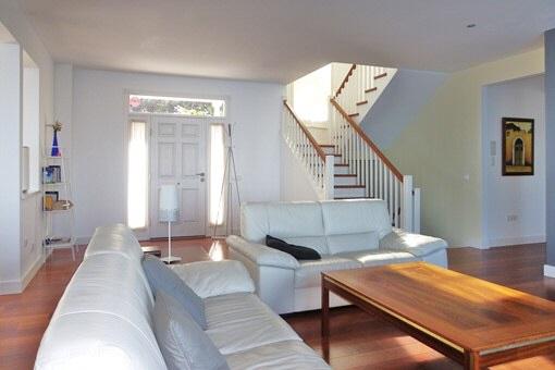 Das große Wohnzimmer mit Eingangsbereich, schöner Treppe und Zugang zur Küche
