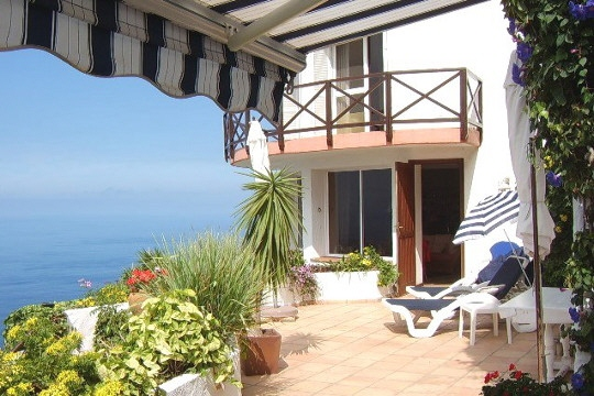 Terrasse mit Sonnenschutz, im Hintergrund die Wohnungen für Gäste