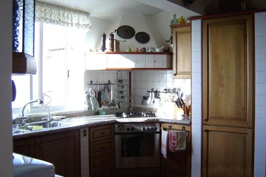 Küche mit angenehmer Arbeitsfläche um den Eckherd mit großer Haube