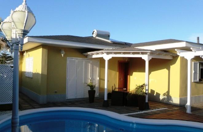 Gesamtübersicht des Chalets am Sonnenuntergang mit Schwimmbad und Solarbatterie am Dach.