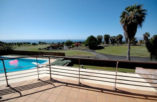 Perfekt: Terrasse, Pool mit Sprungbrett, und das Grün des Golfplatzes vor dem Atlantik