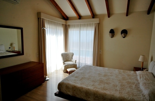 Schlafzimmer mit hoher Balkendecke