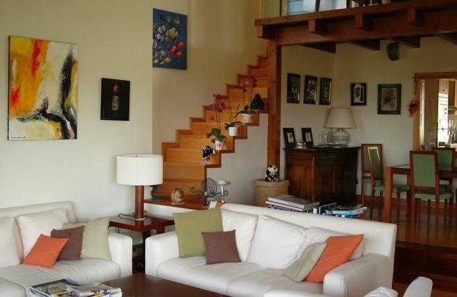 Offener Salon mit Holztreppe zum oberen Schlafzimmer