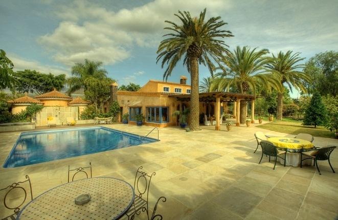 Die Hauptterrase am Pool vor der Villa mit majestätischen Palmen