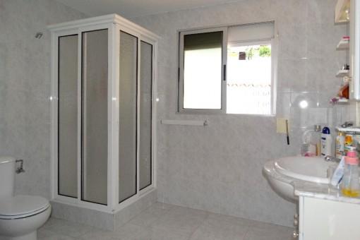 Badezimmer mit Duschkabine und Fenster