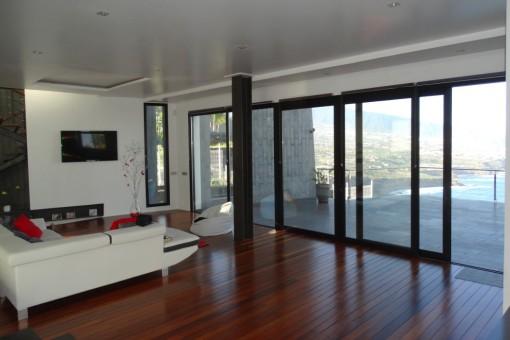 Großes Wohnzimmer mit Parkett und Zugang zur Terrasse
