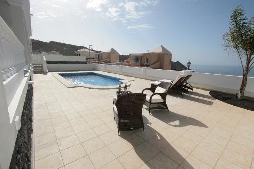 Eine große Terrasse mit Pool und herrlichem Meerblick