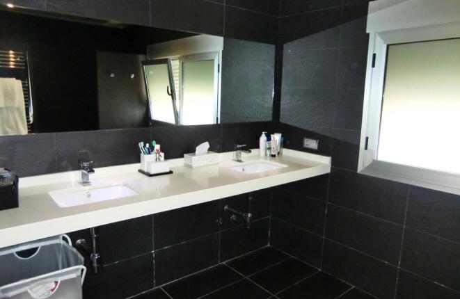 Luxuriöses Badezimmer mit Doppelwaschbecken und Regendusche