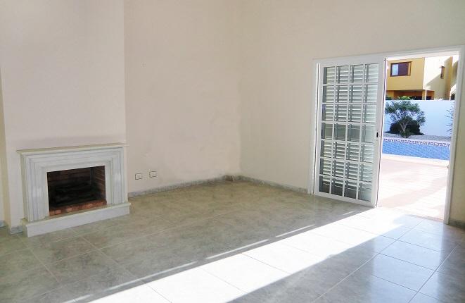Helles Wohnzimmer mit Kamin und Zugang zur Terrasse