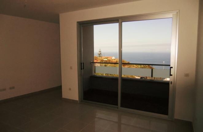 Wohnzimmer mit Zugang zum Balkon mit Meerblick